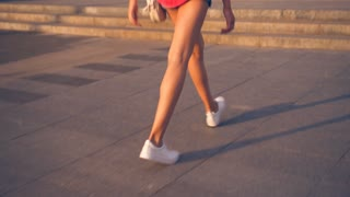 Trendy young girl walking in a hurry in the street