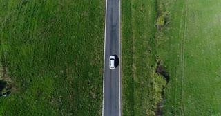 White car driving along farmlands