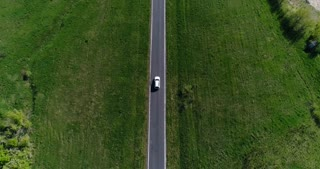 White car moving along country road, aerial view