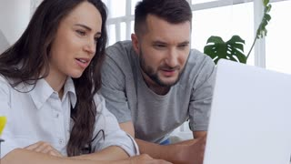 Woman and man talking and looking at laptop