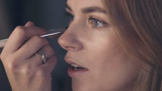 Woman applying brown eye shadow using makeup brush