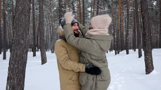 Woman attempting to shake off snow from the hat of her husband