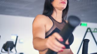 Woman exercising on elliptical trainer