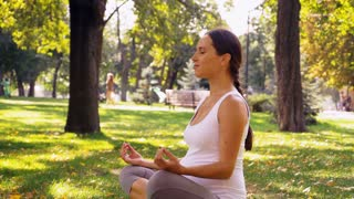 Woman expecting baby meditating in lotus position