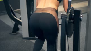 Woman flexing buttock muscles on leg adduction machine