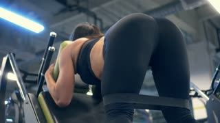 Woman flexing buttock muscles on reverse squat machine