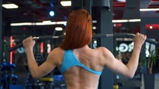Woman flexing muscles on gym machine