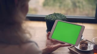 Woman hands holding and touching tablet horizontal with a green screen