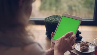 Woman hands using digital, tablet with green screen in cafe