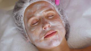 Woman having facial cosmetic mask at spa salon