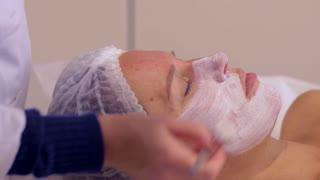 Woman having white facial cosmetic mask at spa salon
