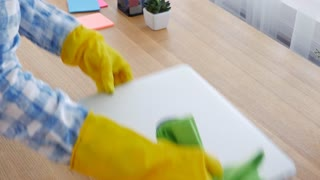 Woman in yellow gloves thoroughly wiping off the dust from laptop