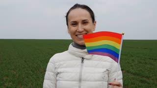 Woman looking at waving rainbow pride stick flag