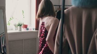 Woman looking in mirror while trying on red sequin dress