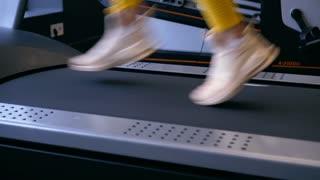 Woman running on treadmill, focus on legs