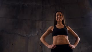 woman showing her trained body at the camera isolated over grey background