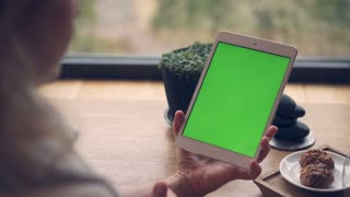 Woman using digital, tablet with green screen