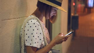Woman using smartphone at night in city