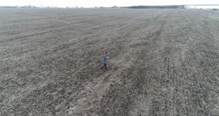 Woman with mobile phone roaming the grey field