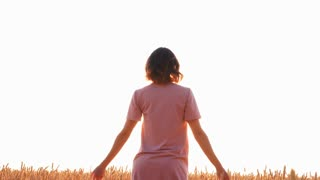 Woman with outstretched hands standing in field