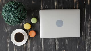 Woman working on a laptop and drinking a cup of coffee with macaroons