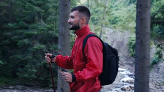 Young active man with poles hiking along mountain river