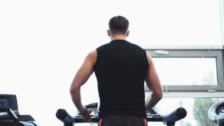 Young athlete walking on treadmill at the gym