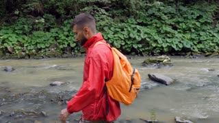 Young bearded hiker stepping rocks in mountain river