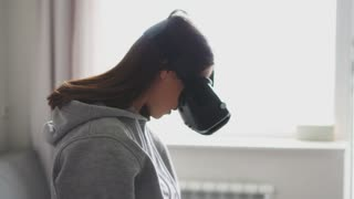 Young brunette in virtual reality glasses orienting at home