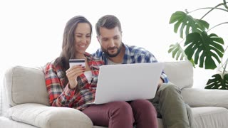 Young couple doing on-line shopping via laptop using credit card at home