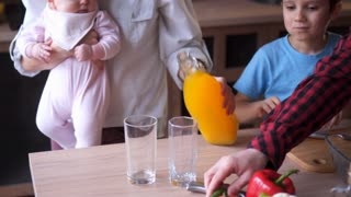 young family cooking at the kitchen and drinking orange juice