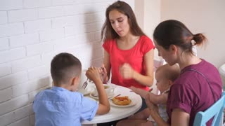 Young family having breakfast together in the kitchen at home