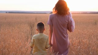 Young family of three walking in wheat field at sunset