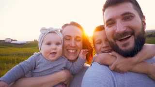 Young family with newborn enjoying walk on sunset