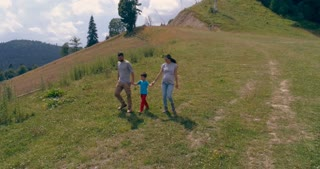 Young father and mother walking with 6 year old son