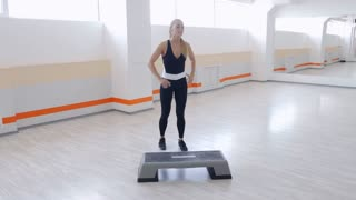 Young sportive woman performing energizing set step workout in gym