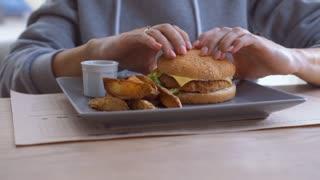 Young woman enjoying a big hamburger at home
