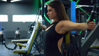 Young woman flexing muscles on cable gym machine