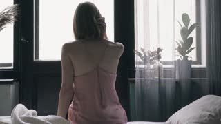 Young woman getting out of bed and looking through the window
