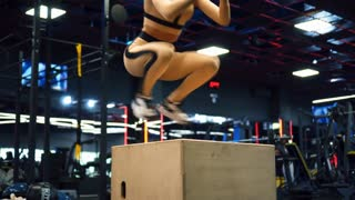 Young woman with perfect body doing set of box jumps