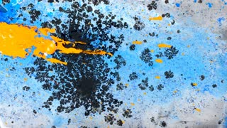Abstract scene of yellow, blue and black ink on blue background