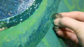Artist scratching her abstract paint with green colors