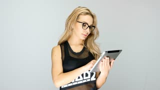 Beautiful blonde woman with a digital tablet in hands over gray background in studio