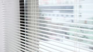 Beautiful woman looks outside the window through the kitchen blinds