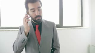 Businessman answering the phone and climbing the stairs in an office building. Communication and finance