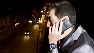 Businessman at the balcony talking on the phone in the night. Communication and mobility