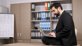 Businessman sitting on the desk and typing on the laptop. Business and finance. Slow motion
