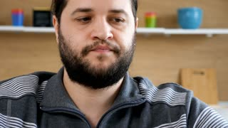 Close up bearded men eating a club sandwich in the kitchen