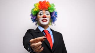 Close up of clown in business suit throwing up a coin in slow motion