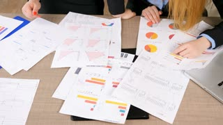 Close up of woman hands analyzing and looking through charts on the table